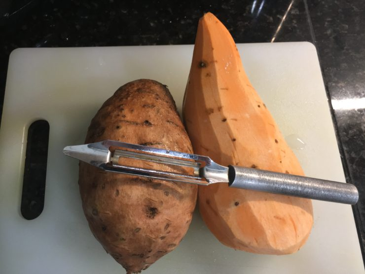 Two large sweet potatoes, partially peeled on a white cutting board with a silver potato peeler.
