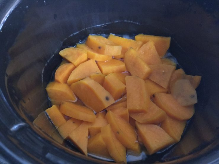 Cooked, peeled, sweet potato chunks in a slow cooker.