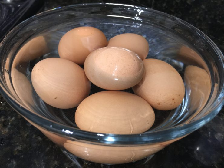 Glass bowl of hard boiled brown eggs in it with cold water.
