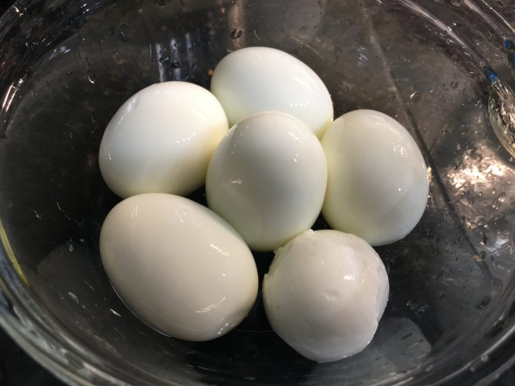 Glass bowl containing 6, peeled hard boiled eggs.