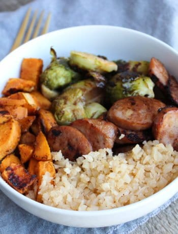 A white bowl with roasted sweet potatoes, roasted brussels, blackened chicken apple sausage, and cauliflower rice in the bowl. A blue towel is placed below the bowl and a gold fork is placed beside the bowl.