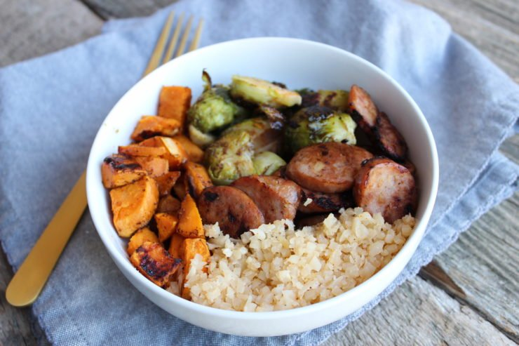 White bowl placed on a blue towel with a gold fork beside the bowl. The bowl contains roasted sweet potato, roasted, halved, Brussels sprouts, blackened chicken apple sausage, and cauliflower rice.
