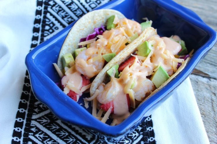 A small blue casserole dish with two Bang Bang Shrimp Tacos in the dish. A white and black Aztec patterned towel sits under the casserole dish.