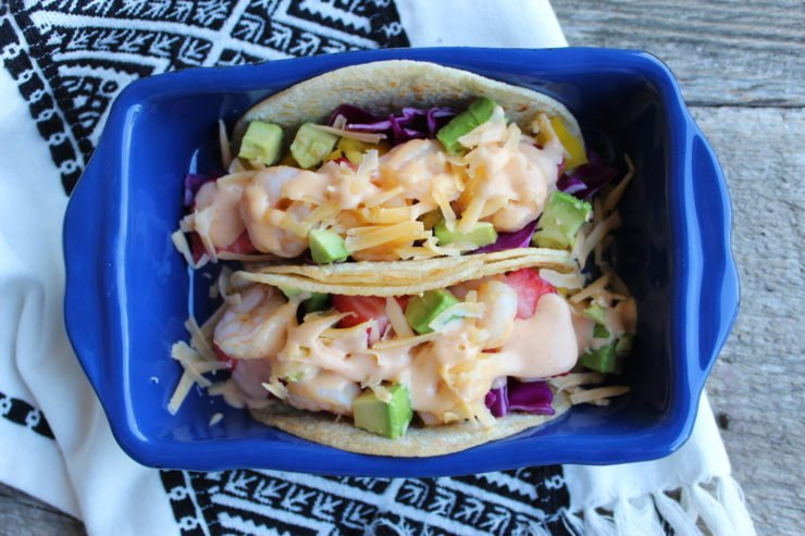 A small blue casserole dish with two, Bang Bang Shrimp Tacos inside. The blue dish sits on a black and white Aztec printed towel on a wood backdrop.
