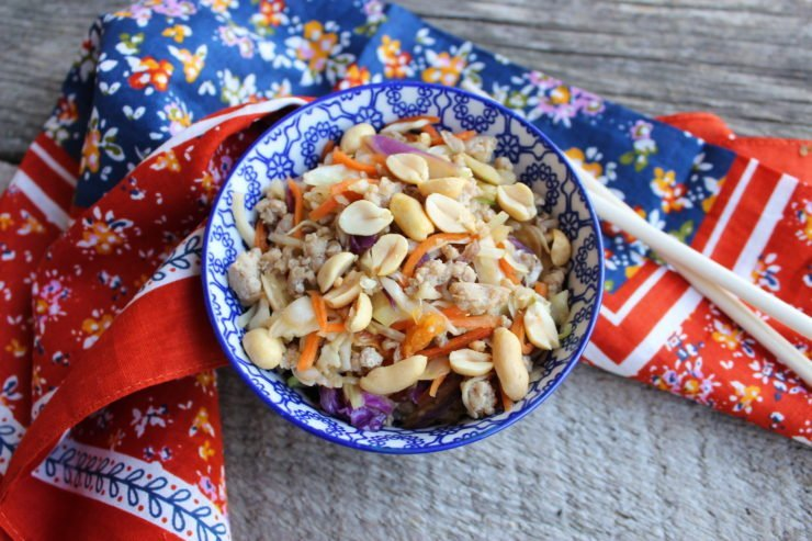 A white and blue floral bowl is filled with Egg Roll in a Bowl with two wood chopsticks placed over the top of the bowl. A floral, multi-colored towel is around the bowl and the bowl sits on a wood back drop.