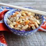 A blue and white floral bowl is filled with Egg Roll in a Bowl with wooden chopsticks placed across the top of the bowl. A multi colored floral towel is around the bowl and the bowl is on a wood backdrop.