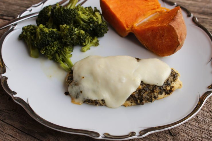 A white plate with silver detail contains one chicken breast with Basil Pesto and melted mozzarella on it, along with steamed broccoli and a sweet potato. The plate has a silver fork placed on it, and the plate sits on a wood board.