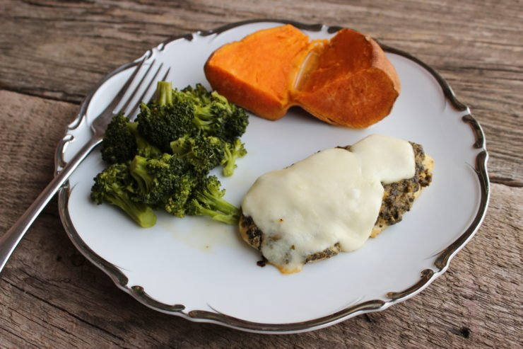 A baked chicken breast with basil pesto and melted mozzarella, steamed broccoli, and baked sweet potato on a white plate with silver detail. The plate has a silver fork beside it and the plate sits on a wood backdrop.
