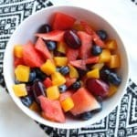 A white bowl on a black and white Aztec towel. The white bowl is filled with diced watermelon, peaches, blueberries, and purple grapes.