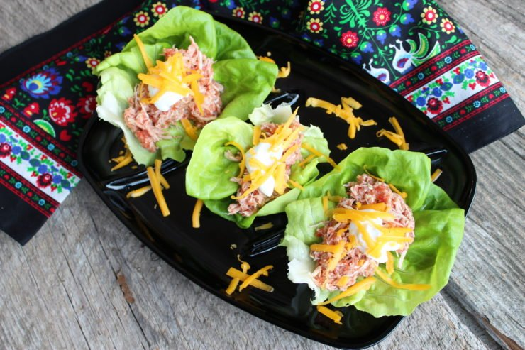 Chicken tacos in butter lettuce wraps sit on a black platter with a floral, multi colored towel around the platter. The platter is sitting on a wooden board.