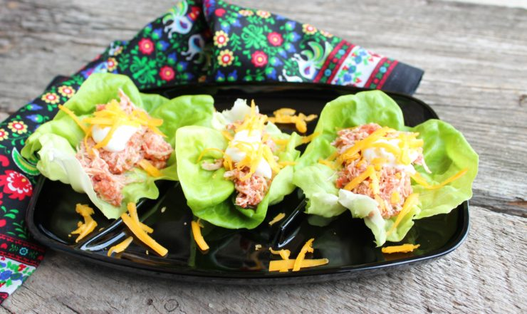 A black platter with three butter lettuce wraps with Instant Pot Chicken inside. A multi colored floral towel is around the platter and the platter sits on a wood board.