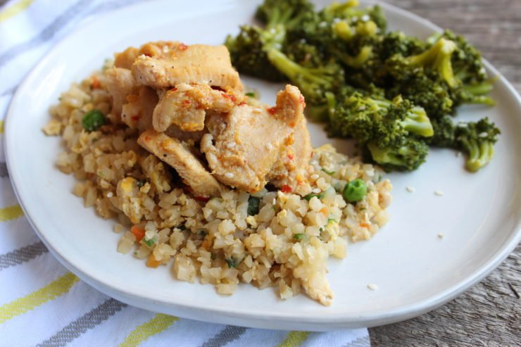 A white plate with Paleo Orange Chicken with cauliflower fried rice and seasoned steamed broccoli on the plate. A white, yellow, and gray striped towel is placed beside the plate and it all sits on a board.