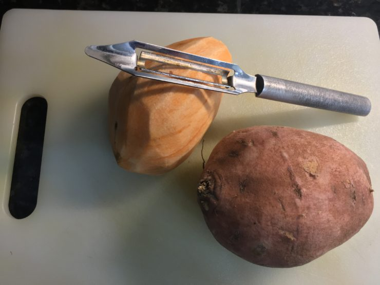 Two sweet potatoes placed on a white cutting board with one potato peeled and a silver potato peeler on the potato.