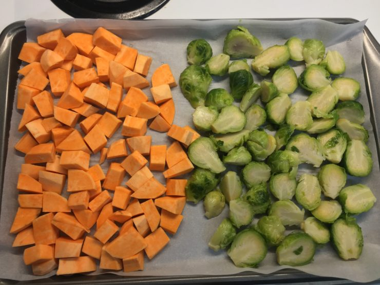 Sheet pan lined with parchment paper with peeled and chunked sweet potato on the left and halved brussles sprouts on the right.