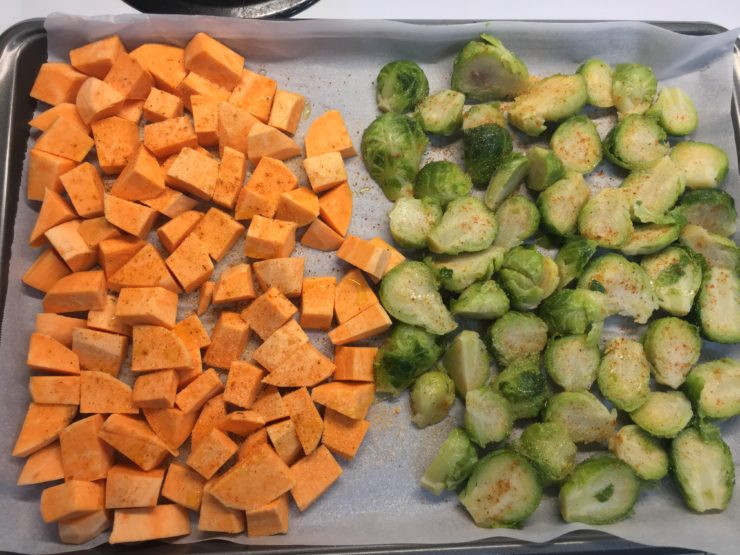 Peeled and chunked sweet potatoes and halved brussels sprouts on a sheet pan that has been lined with parchment paper. The vegetables are seasoned.
