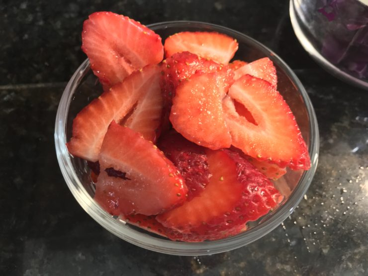 Small glass bowl with sliced strawberries inside. The strawberries have been sliced into thinner pieces from top to bottom.