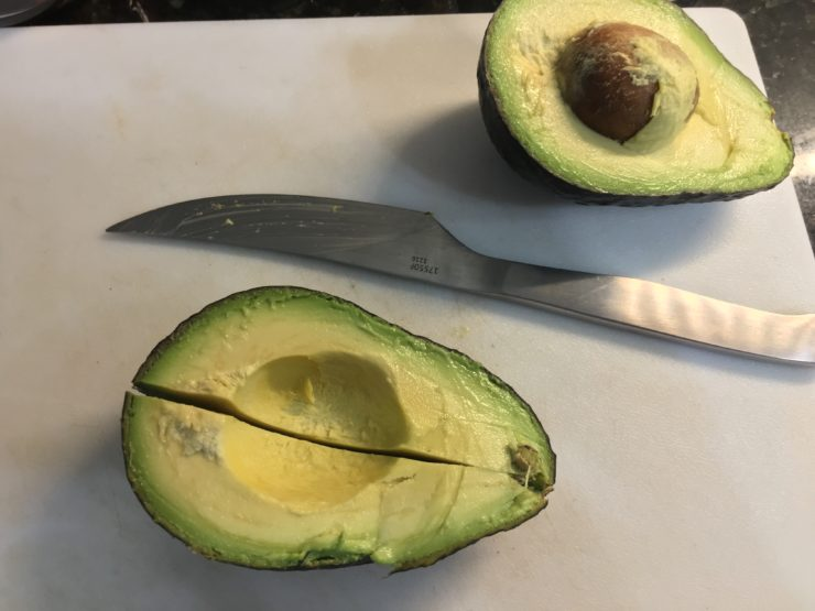 White cutting board with an avocado sliced open and one half of the avocado cut into two pieces lengthwise. A silver pairing knife is laying on the cutting board.