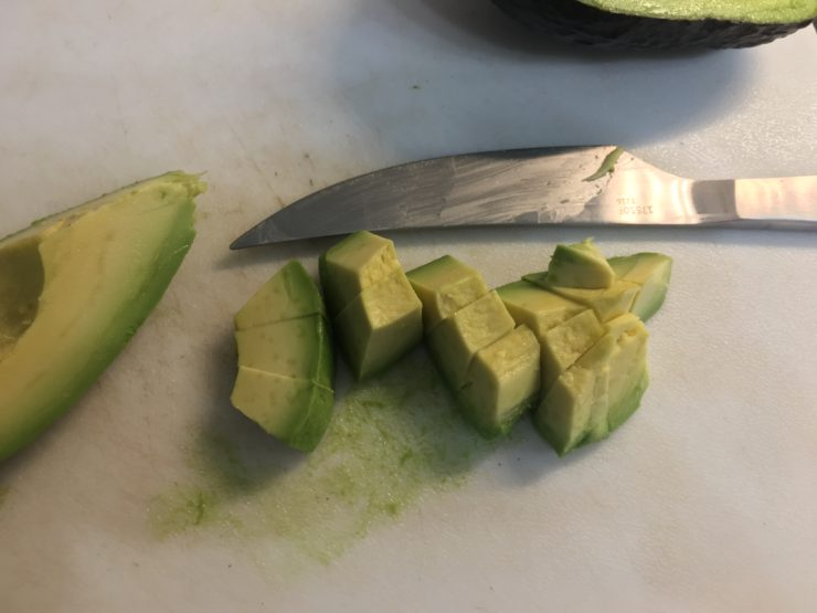 White cutting board with diced avocado on the cutting board and a silver pairing knife on the board.