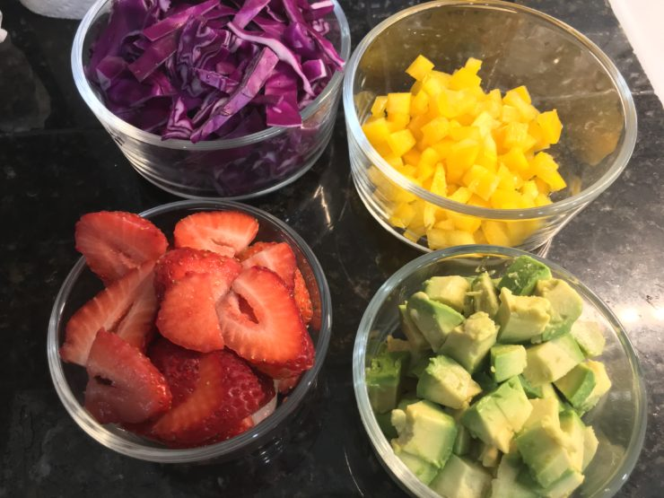 Four small glass bowls with shredded red cabbage, diced yellow bell pepper, sliced red strawberries, and diced green avocado in them.