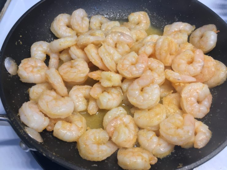Small black skillet with cooked, seasoned, small shrimp inside.