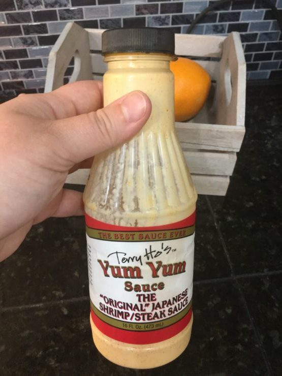 A hand holding a bottle of Japanese Yum Yum Sauce.