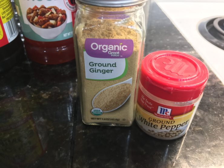 A container of Organic ground ginger and ground white pepper on a black, granite counter top.