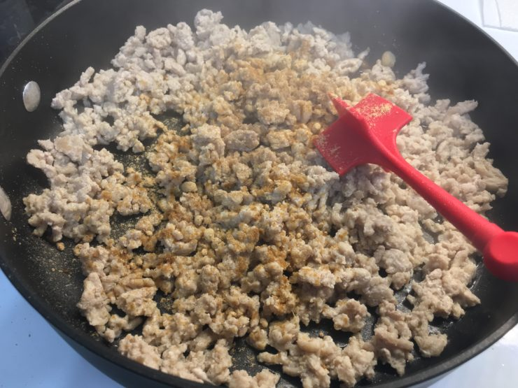 A large black skillet with ground chicken seasoned with ground ginger and ground white pepper.