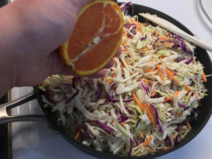 A large black skillet with tri-colored coleslaw in the skillet and half of an orange held over the skillet.