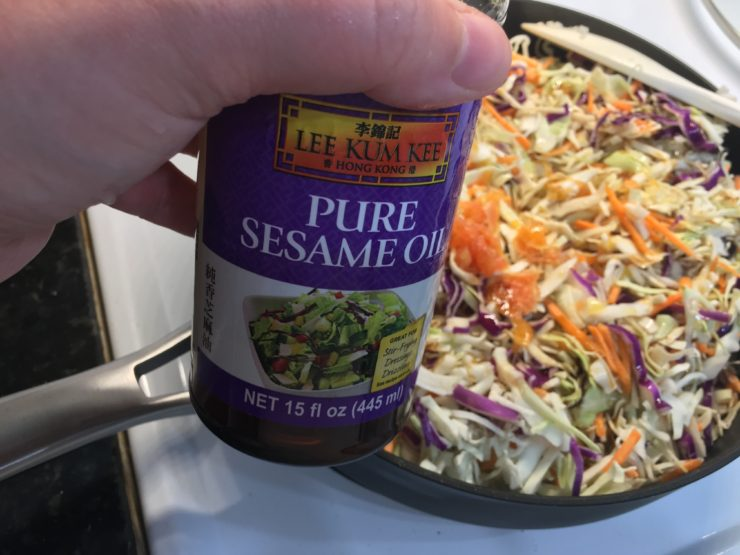 A large black skillet with tri-colored coleslaw and orange pulp in the skillet. A hand is holding a bottle of pure sesame oil beside the skillet.
