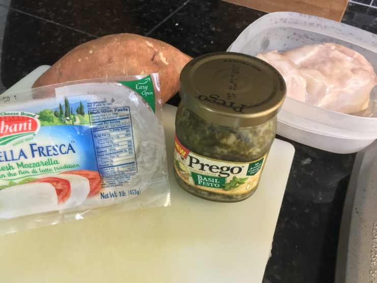 A package of fresh mozzarella cheese, a jar of Prego Basil Pesto, and a large sweet potato sits on a white cutting board with a container of chicken breast to the right of the cutting board.