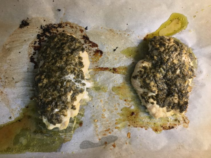 A parchment lined sheet pan with two baked chicken breasts covered in basil pesto.