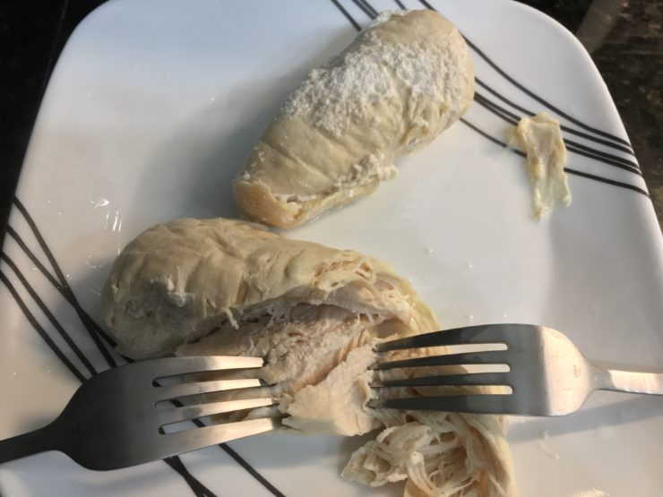 A white plate with black stripes and two cooked, boneless, skinless chicken breasts with two forks shredding the chicken.