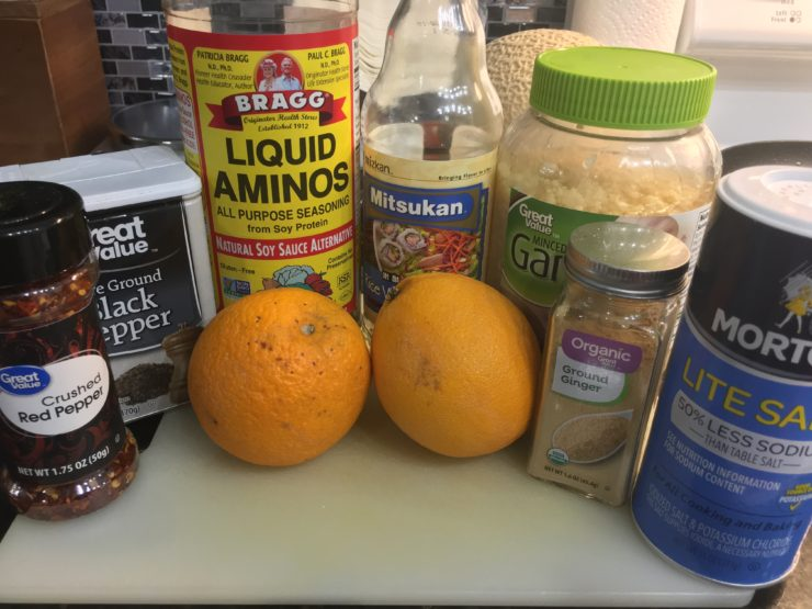 A white cutting board with all ingredients to make Orange Chicken. The white cutting board has a bottle of crushed red pepper, ground black pepper, salt, ground ginger, minced fresh garlic, liquid aminos, rice vinegar, and two oranges.