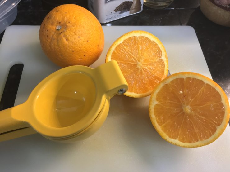 A white cutting board with one whole orange, an orange sliced in half, and a yellow citrus squeezer.