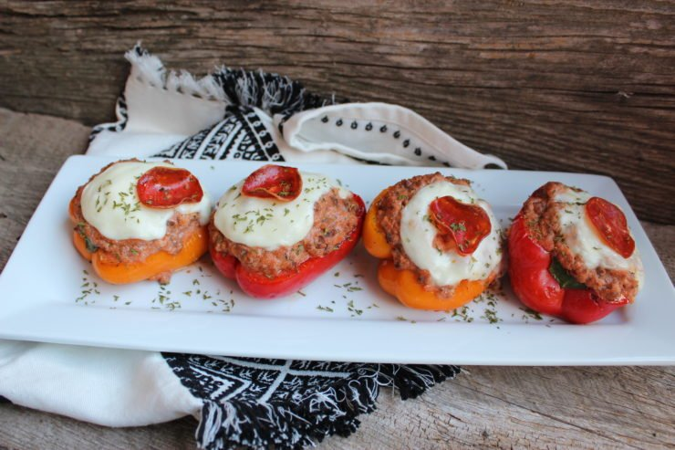 A long, white platter sits on a wooden backdrop with a black and white towel underneath. Low Carb Italian Stuffed Bell Peppers sit in the center of the platter.