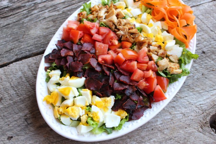 An oval, white platter with lettuce, boiled egg, crumbled turkey bacon, diced tomato, diced grilled chicken, and carrot ribbons to create a cobb salad.