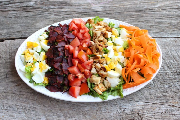A long, white platter filled with Easy Cobb Salad sits in the center of a wooden backdrop.