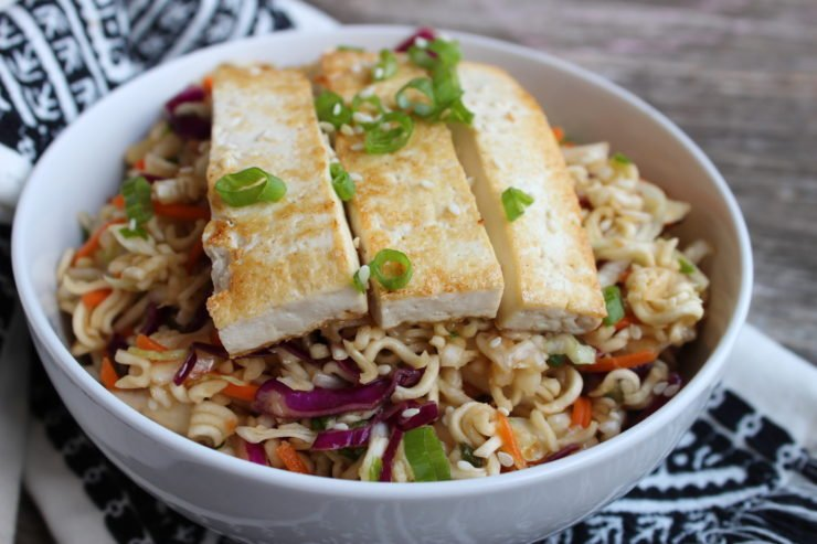 A white bowl with Easy Top Ramen Salad in it, topped with fried striped of tofu. The bowl is sitting on a black and white aztec towel and the towel is on a wooden board.