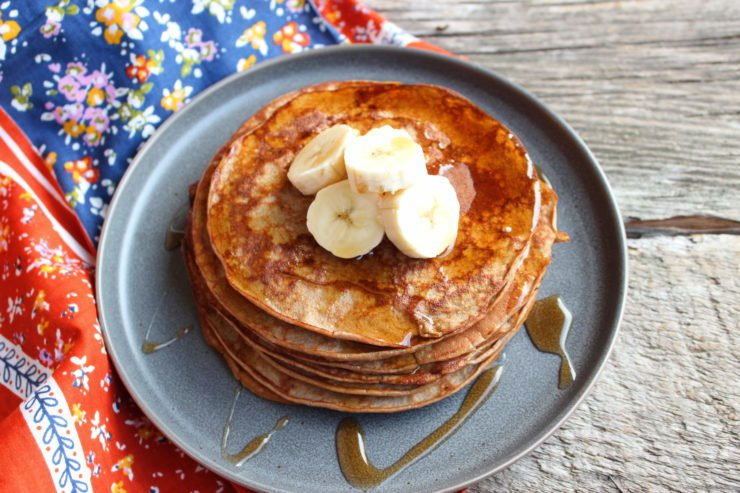 A pewter plate with a stack of Banana Protein Pancakes on the plate. The pancakes are topped with sliced banana and drizzled with syrup. A multi colored floral towel is placed beside the plate and it all sits on a wooden board.