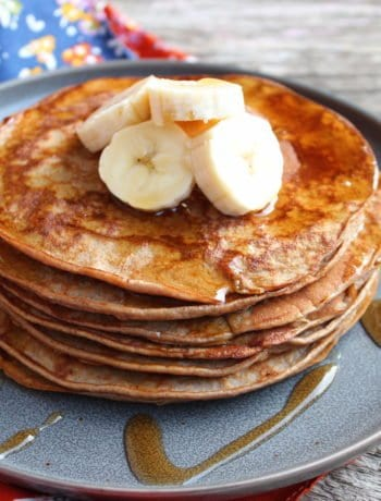 A pewter plate with a stack of Banana Protein Pancakes on the plate that have been topped with sliced banana and drizzled with syrup. A floral, multi colored towel is placed beside the plate and the plate sits on a wooden board.