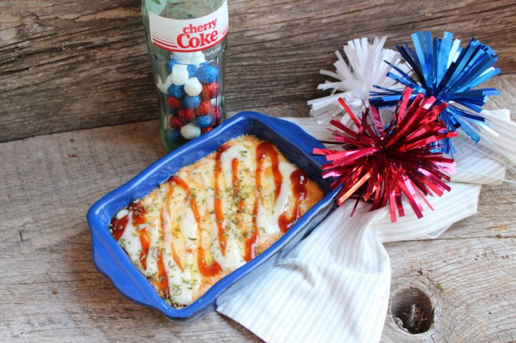 A small blue casserole dish with BBQ Ranch Chicken Dip in the dish. A white and gray striped towel is under the casserole dish and decorative red, white, and blue, balls sit beside the dish and a Coke bottle with red, white, and blue decorative balls inside sits behind the casserole dish. Everything is placed on a wooden backdrop.