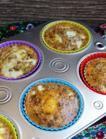 A silver, half dozen muffin tin with multi colored silicone muffin liners and egg muffins inside. The tin is sitting on a wood backdrop with a multi colored floral towel underneath.