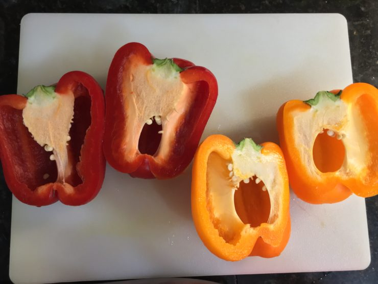 White cutting board with one red bell pepper and one orange bell pepper cut in half lengthwise on the board.