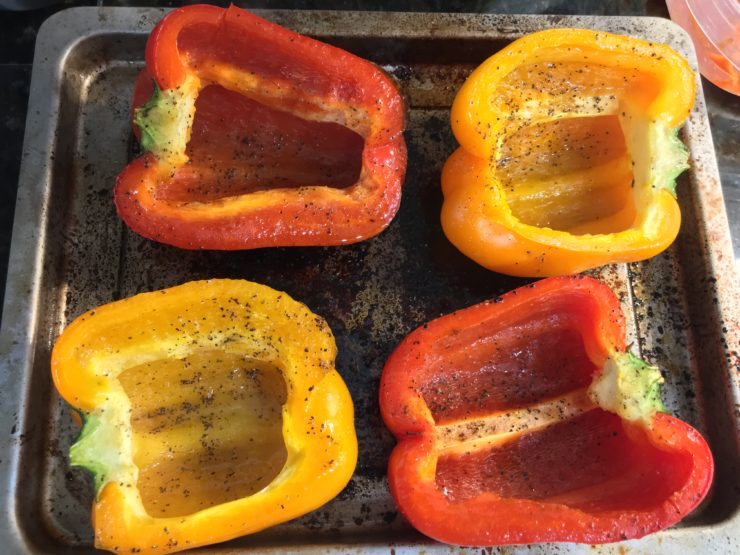 Halved and seeded bell peppers on a baking sheet that have been seasoned with salt, pepper, and drizzled lightly with olive oil.