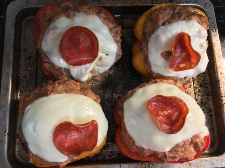 A baking sheet with four baked bell pepper halves, stuffed with meat mixture and topped with freshly sliced and melted mozzarella cheese and one slice of turkey pepperoni.