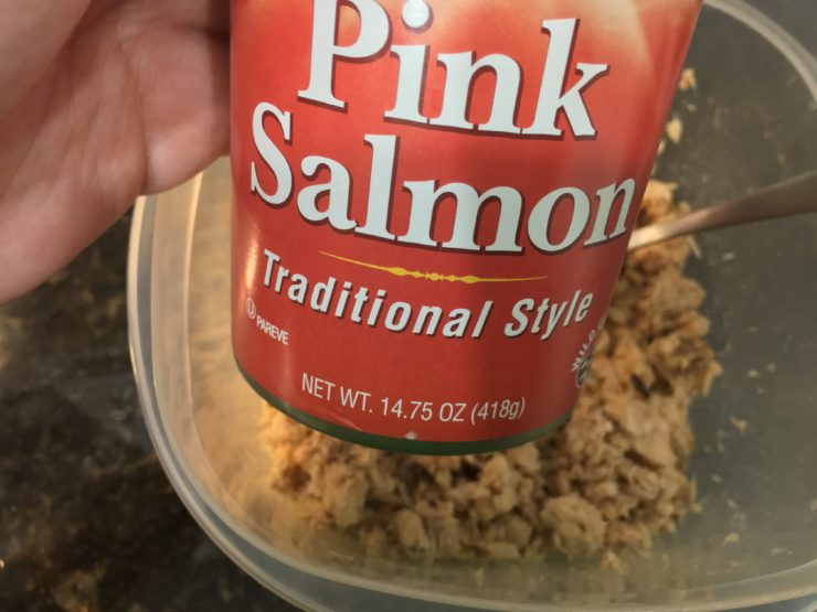 A hand holding a can of pink salmon with a bowl in the background that has canned, pink salmon in it.