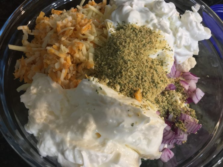 A glass mixing bowl with raw broccoli florets, raw cauliflower florets, minced red onion, and shredded Colby Jack cheese and shredded white sharp cheddar cheese and plain, nonfat Greek yogurt, mayo, and dry ranch dip seasoning.