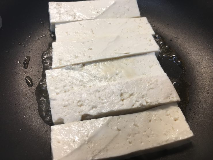A black skillet with heated sesame oil in it and six slices of extra firm, organic tofu cut into strips, frying in the pan.