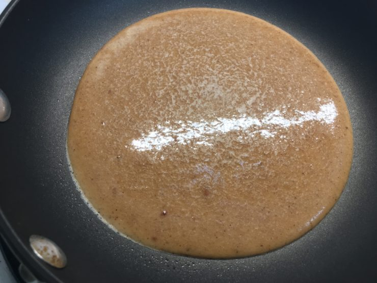A small, black skillet with banana pancake mix in the skillet.