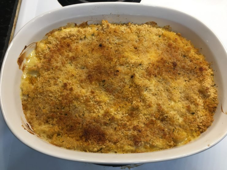 A white casserole dish with baked, Creamy Scalloped Chicken Casserole in the dish.